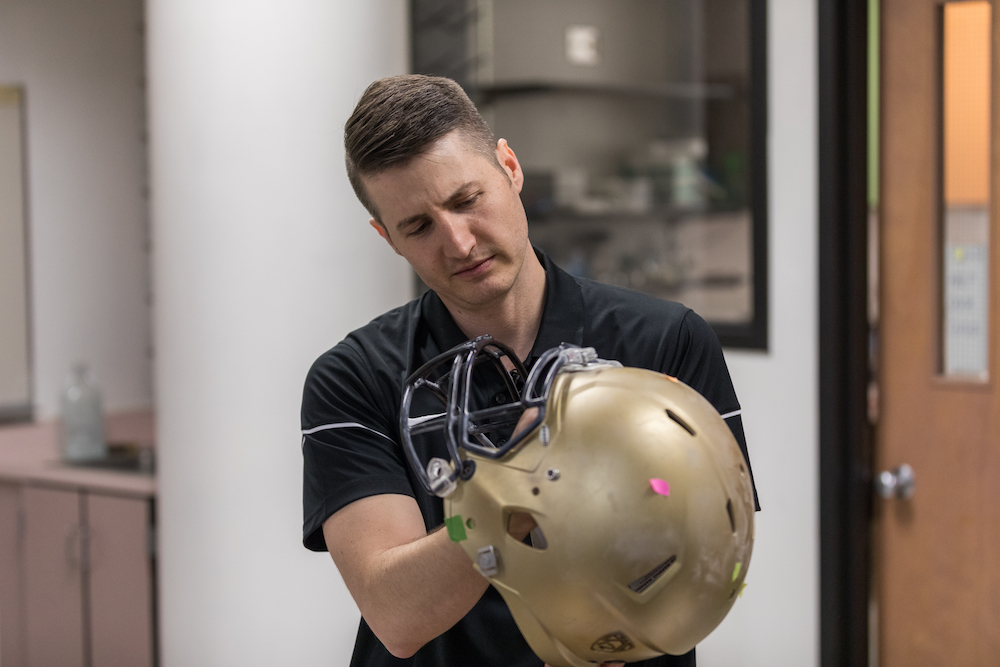 Associate professor Chris Yakacki examines a football helmet